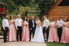 Groom and bride stand with groomsman and bridesmaid outside. Newlyweds kissing and friend clap. Wedding day.  royalty free stock photos