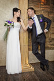 Groom and the bride  stand near  column Royalty Free Stock Images