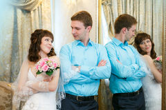 Groom and the bride stand near a mirror with a gold frame Royalty Free Stock Images