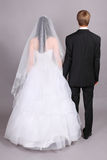 Groom and bride stand their backs to camera royalty free stock image