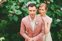 Groom and bride standing near bush with flowers Royalty Free Stock Photography