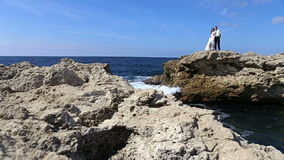 Groom bride standing on a rock, kissing stock footage