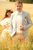 Groom and bride standing in tall grass Stock Images
