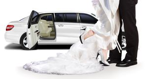 Groom and bride standing beside white limo Stock Photography