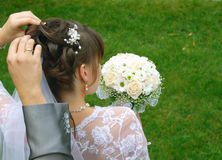 Groom and bride. The groom straightens her hair bride with a bouquet Stock Images