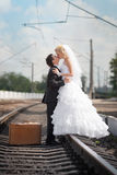 Groom and  bride with a suitcase at railway station Royalty Free Stock Photo