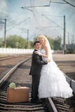 Groom and  bride with a suitcase at railway station Royalty Free Stock Photography