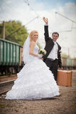 Groom and  bride with a suitcase at railway station Stock Photography