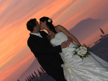 Groom and bride sunset kissing Stock Photos
