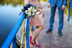 Groom and bride together on wedding day. Newlyweds couple, blurred background, focus on bouquet.  Royalty Free Stock Images