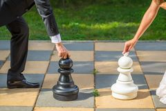 Groom and bride together on wedding day playing outdoor chess. stock photography