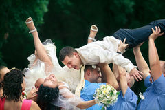 Groom and bride  tossed into air Royalty Free Stock Photography