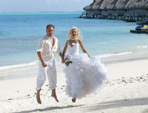 The groom and the bride on the tropical beach jumps at sea edge. Stock Photos