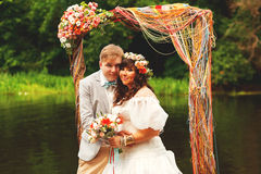 Groom and bride under arch near pond Royalty Free Stock Images