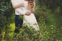 Groom and bride in a veil standing and holding hands Stock Images
