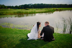Groom and the bride walk near the lake on their wedding day Stock Photography