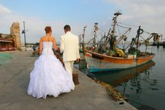 The groom and the bride walk near the sea. Royalty Free Stock Photos