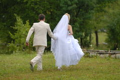 Groom and the bride during walk in park. The careful groom supports a dress of the bride Royalty Free Stock Photography