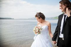 Groom and bride is walking on the bank Royalty Free Stock Photography