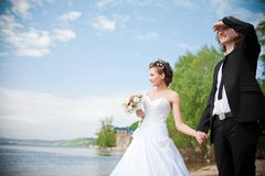 Groom and bride is walking on the bank Stock Photo