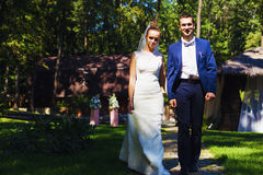 Groom and bride walking on path Royalty Free Stock Image