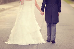 Groom and bride walking. Bride and groom walking on road Royalty Free Stock Images