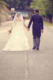 Groom and bride walking on the road Stock Images