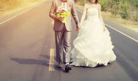 Groom and bride walking in the road go to marry. Couple wedding walking in the road go to marry Royalty Free Stock Photo