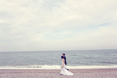 Groom and bride walking on the shore Royalty Free Stock Image