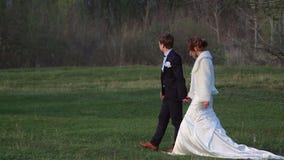 Groom with bride walking in the woods in spring stock footage