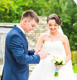 Groom and bride is wearing a ring on the finger,  wedding ceremony. Gold, symbol, religion, love. Royalty Free Stock Images