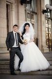 Groom and the bride with a wedding bouquet near a white column Stock Image