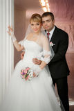 Groom and the bride with a wedding bouquet stand near  column Stock Image