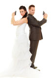Groom and bride in wedding outfit holding guns Royalty Free Stock Photo