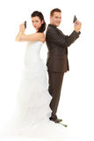 Groom and bride in wedding outfit holding guns Stock Photography