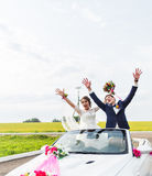 The groom and the bride in a white convertible car Stock Photography