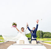 The groom and the bride in a white convertible car royalty free stock photo