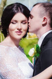 Groom and bride in a white dress in the spring garden Royalty Free Stock Images