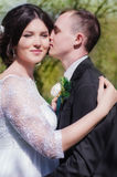 Groom and bride in a white dress in the spring garden Stock Images