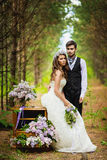 The groom with the bride in the wood with a lilac Stock Photo