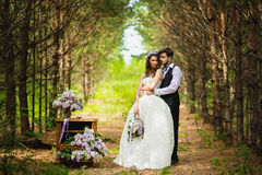 The groom with the bride in the wood with a lilac Stock Image