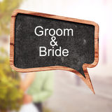 Groom and Bride word concept on speech bubbles from wood on blur background Royalty Free Stock Images