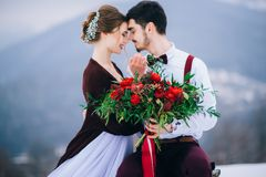 Walk the groom and the bride in the Carpathian mountains. Groom in a brown and bride in burgundy in the mountains Carpathians Royalty Free Stock Images
