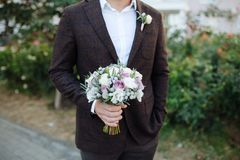 The groom in a brown suit with a beautiful bouquet of white and purple roses. Waiting for the bride on the street. white shirt. stock photos
