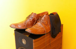 Groom brown wedding shoes on speaker. Yellow background. Stock Images