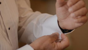 Groom button the cuffs on his white shirt stock video footage