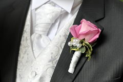 Groom with button hole flower. Smart wedding suit of groom with pink carnation flower in lapel button hole royalty free stock photography