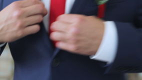 Groom buttoning on his jacket close-up stock video footage