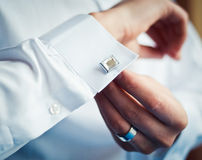 Groom buttons on his shirt cuffs.  Stock Image