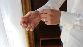Groom buttons on his shirt cuffs stock video footage